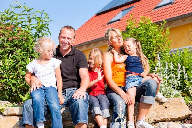 Família na frente de casa ou casa
