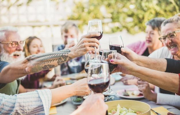Família na moda feliz torcendo com vinho tinto no jantar de churrasco ao ar livre