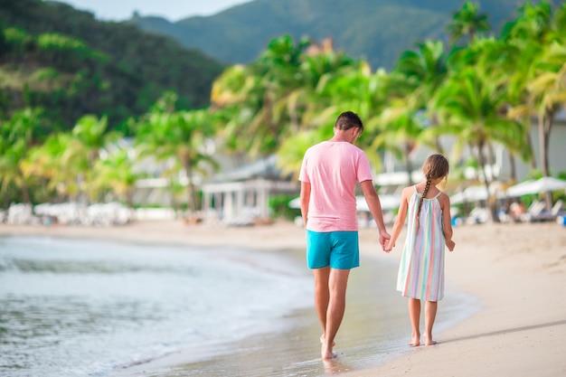 Família na praia tropical que anda junto na praia tropical da baía de carlisle com água branca do oceano da areia e da turquesa na ilha de antígua nas caraíbas.