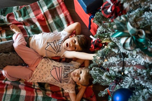 Família na véspera de natal. kids crianças sob a árvore de natal com caixas de presente. sala decorada com lareira tradicional. acolhedora noite quente de inverno em casa.