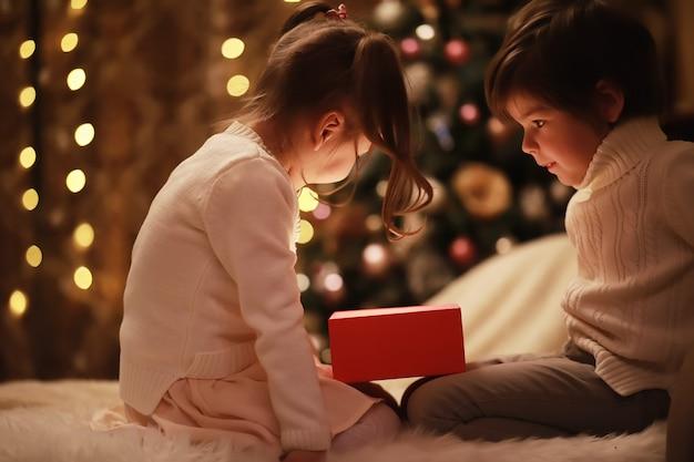 Família na véspera de natal na lareira. crianças abrindo presentes de natal. crianças debaixo da árvore de natal com caixas de presente. sala decorada com lareira tradicional. aconchegante noite quente de inverno em casa.