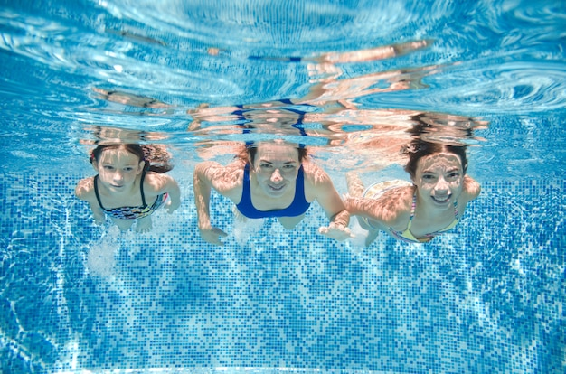 Família nada na piscina debaixo d'água, feliz mãe ativa e as crianças se divertem debaixo de água, fitness e esporte com crianças nas férias de verão