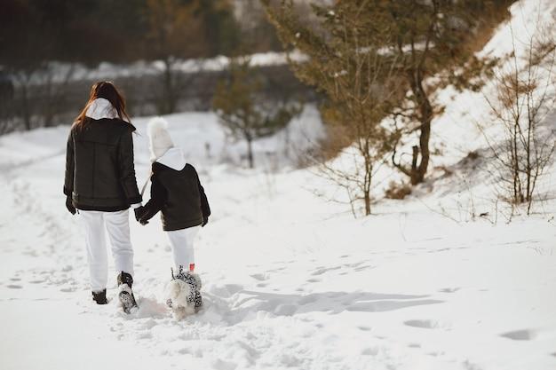 Família nas férias de natal em família. mulher e menina em uma floresta. pessoas caminham.