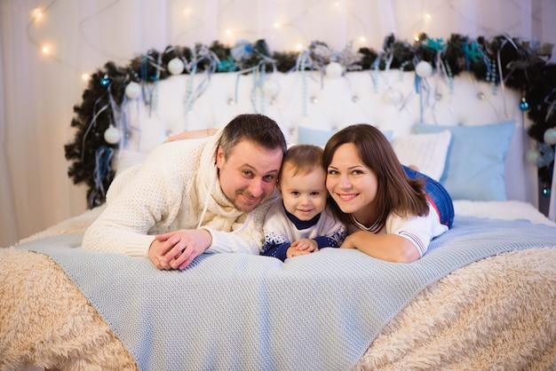 Família natal feliz mãe, pai e filho deitado na cama. enjoyng abraços de amor, férias pessoas.