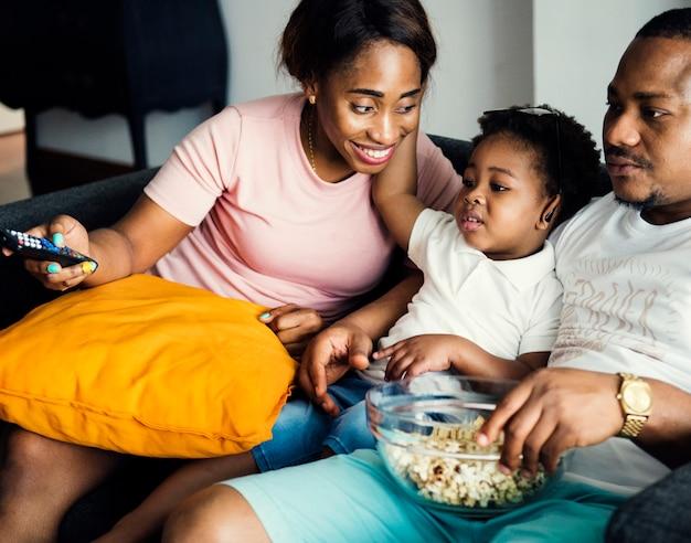 Família negra comendo pipoca enquanto assiste filme em casa