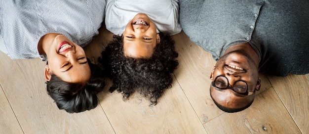 Família negra deitada em um espaço de design de piso de madeira