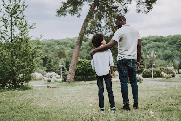 Família negra descansando na natureza e olhando uns aos outros