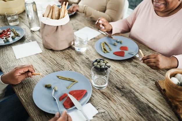 Família negra feliz almoçando em casa