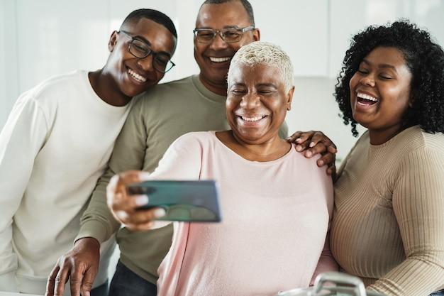 Família negra feliz tirando uma selfie com o celular na cozinha de casa