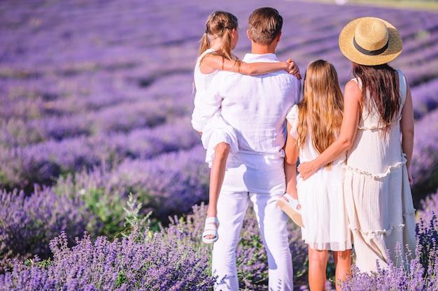Família no campo de flores de lavanda ao pôr do sol com vestido branco e chapéu