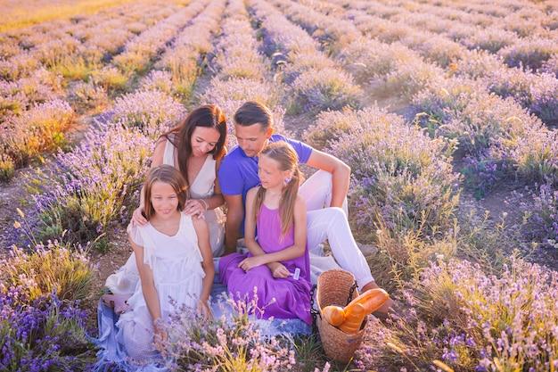 Família no campo de flores de lavanda ao pôr do sol em vestido branco e chapéu