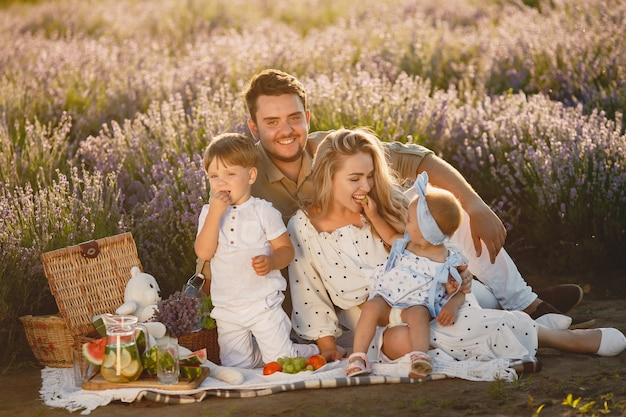 Família no campo de lavanda. pessoas em um piquenique. mãe com filhos come frutas.