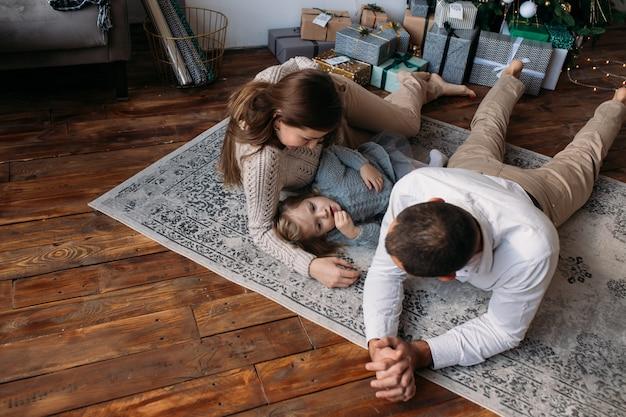 Família no chão jogando em casa perto de árvore de natal