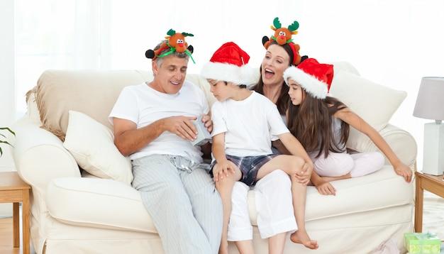 Família no dia de natal olhando seus presentes em casa
