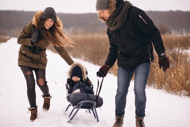 Família no inverno com trenó de filho