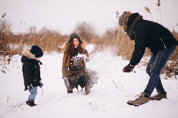 Família no inverno jogando com neve no parque