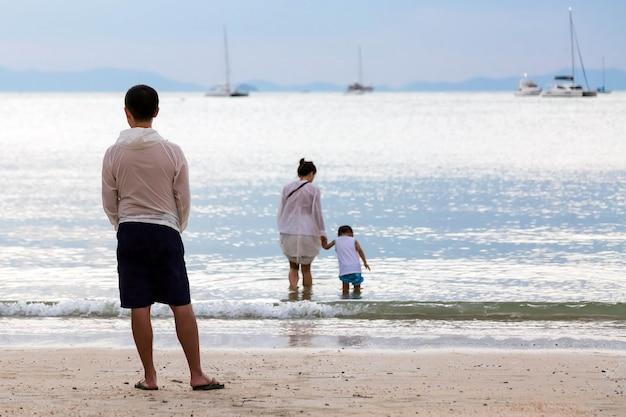 Família no mar. um pai observa sua esposa e filho entrarem na água da praia
