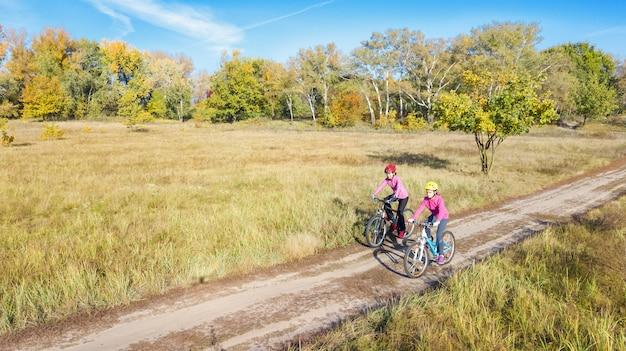 Família no outono de bicicleta, andar de bicicleta ao ar livre, mãe ativa e criança em bicicletas, vista aérea da família feliz com criança no parque outono de cima, conceito de esporte e fitness