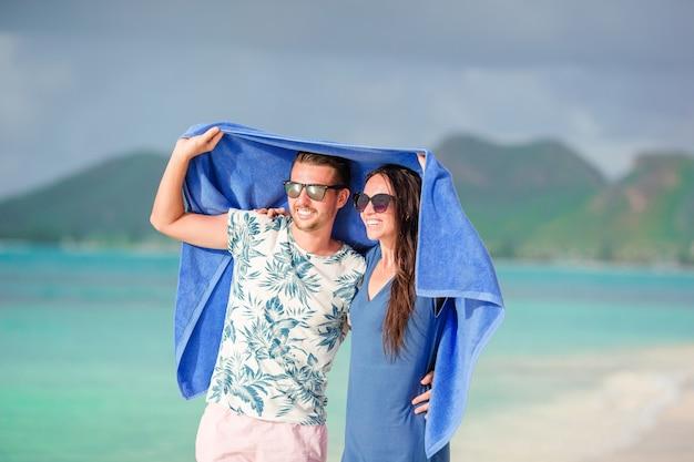Família nova de dois na praia tropical com toalha. praias tropicais remotas e países. conceito de viagens