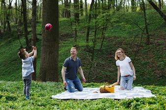 Família nova feliz joga com uma bola sobre a manta durante um piquenique no parque