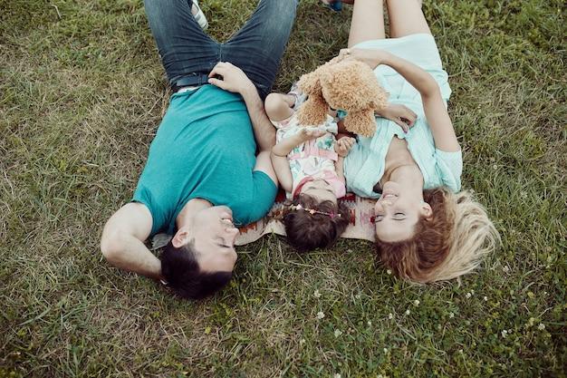 Família nova feliz que passa o tempo junto fora na natureza verde.