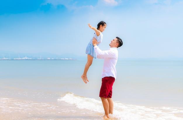 Família nova feliz que relaxa junto na praia, pessoa que tem o divertimento em férias de verão.