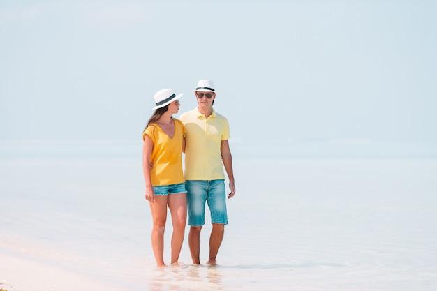 Família nova na praia branca durante férias de verão.