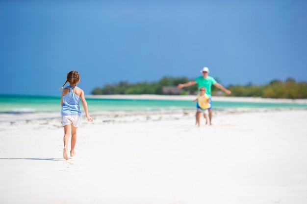 Família nova que aprecia férias de verão da praia. crianças e papai juntos na praia