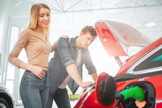 Família nova que compra o primeiro carro elétrico na sala de exposições