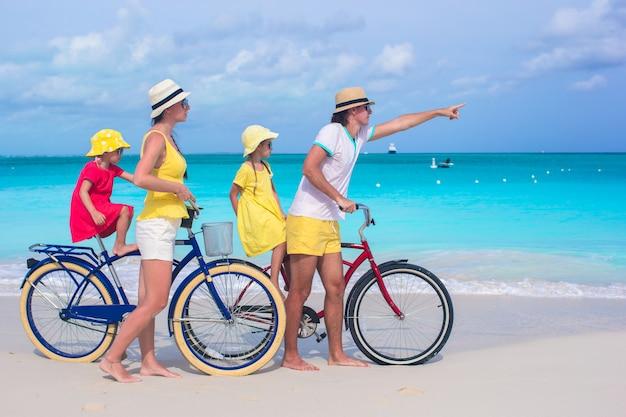 Família nova que monta bicicletas em uma praia tropical
