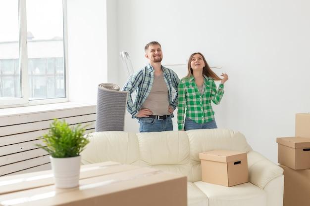 Família, novo apartamento e conceito de relocação - jovem casal se mudando para a nova casa.