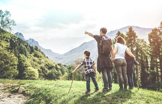 Família num prado verde olhando para o panorama da montanha