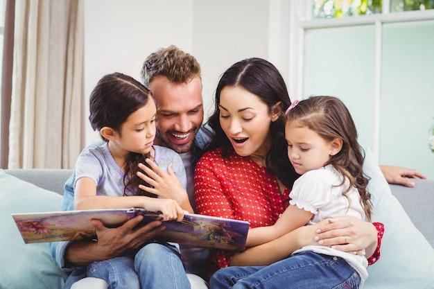 Família olhando no livro de imagens enquanto está sentado no sofá