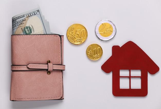 Família, orçamento doméstico. o conceito de comprar ou pagar a habitação carteira com dinheiro, estatueta de casa em um branco