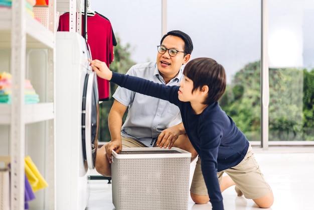 Família pai asiático e filho menino se divertindo fazendo tarefas domésticas, lavando roupas sujas na máquina de lavar roupa juntos na lavanderia em casa