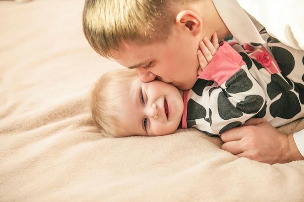 Família, pai e filha juntos em casa abraçando belos e felizes close-ups
