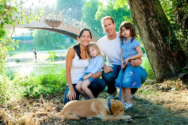 Família pai mãe filhos e cachorro ao ar livre