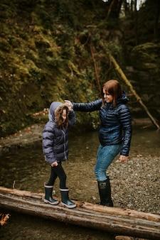 Família para acampar mãe e filha caminhando na floresta