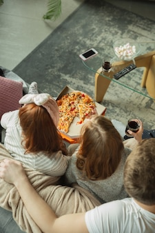 Família passando bons momentos juntos em casa, parece feliz e alegre. mãe, pai e filha se divertindo, comendo pizza, assistindo a uma partida de esporte ou tv. união, conforto do lar, amor, conceito de relações.