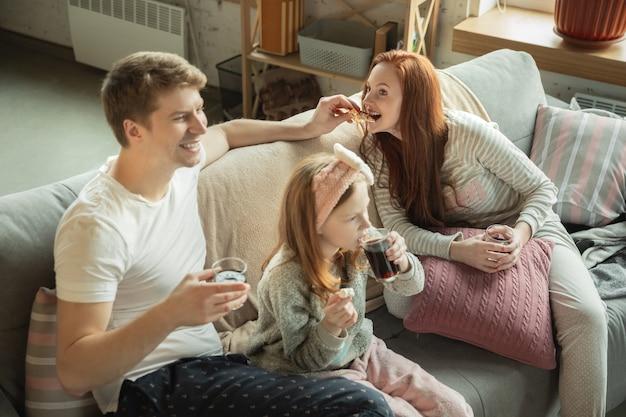 Família passando bons momentos juntos em casa parece feliz e alegre. mãe, pai e filha