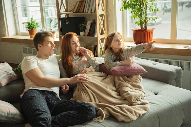 Família passando bons momentos juntos em casa, parece feliz e animado. mãe, pai e filha se divertindo, comendo pizza, assistindo a campeonatos esportivos na tv. união, conforto do lar, conceito de amor.
