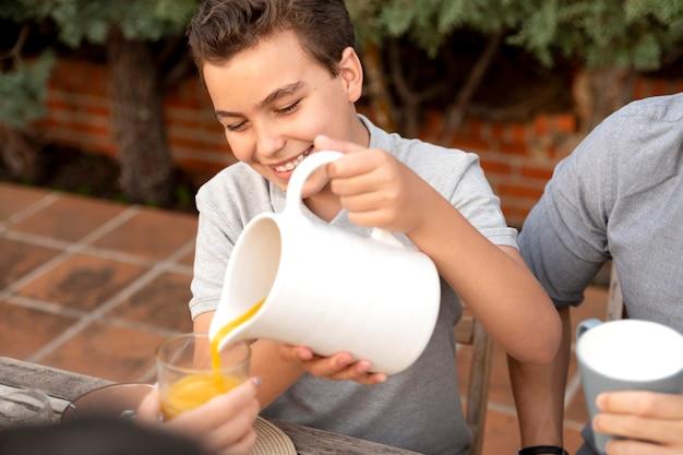 Família passando um tempo junta ao ar livre bebendo suco de laranja