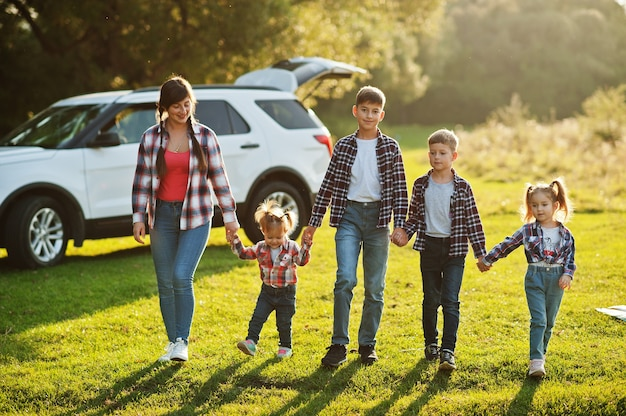 Família passando um tempo juntos. mãe com quatro filhos em pé e de mãos dadas contra o carro suv branco.