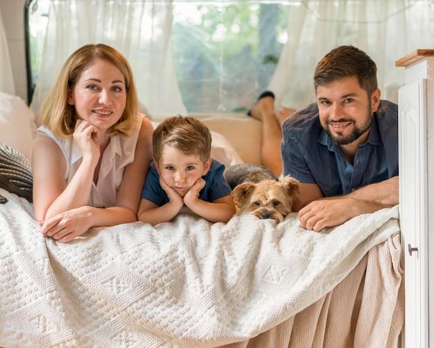 Família passando um tempo na cama em uma caravana com seu cachorro