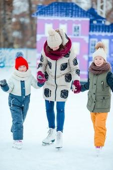 Família patinar na pista de gelo. mãe e filhos aprendendo a andar de skate no inverno