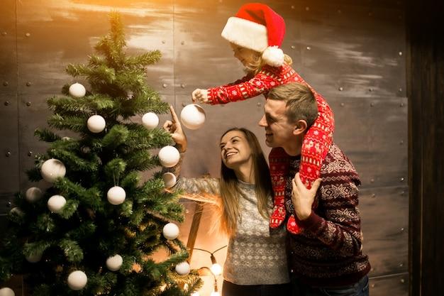 Família pela árvore de natal com pequena filha em um chapéu vermelho