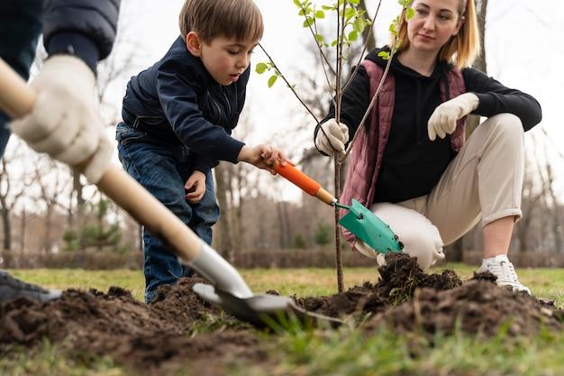 Família plantando juntos uma árvore