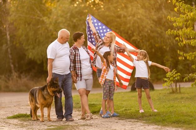 Família posando ao ar livre com a bandeira americana