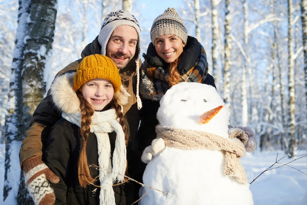 Família posando com boneco de neve