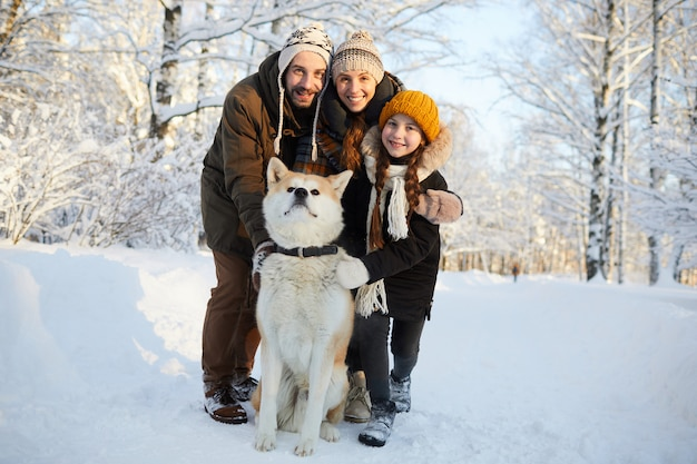 Família posando com cachorro ao ar livre